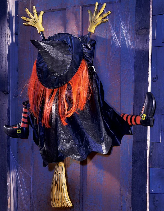 A decorative witch on splattered on a front door, as if she crashed into the door off her broom